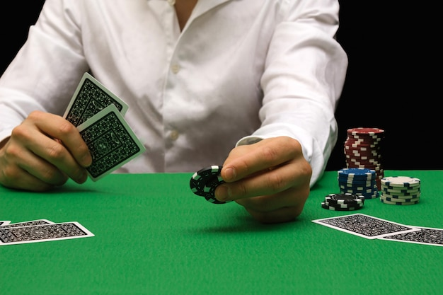 夜のカジノでポーカーをし、チップでお金を賭けている人。コピースペースと黒の背景。ギャンブル、勝ち、負け、楽しみ、富、勝利の概念。