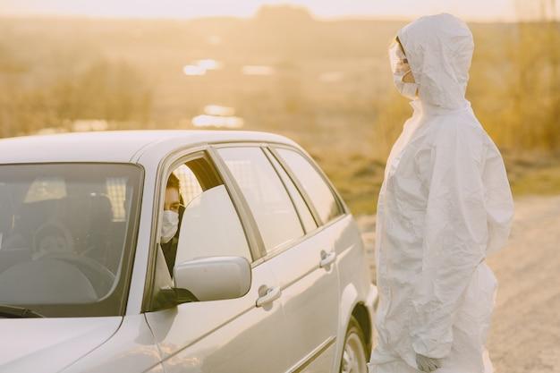 防護服を着た人が温度をチェック