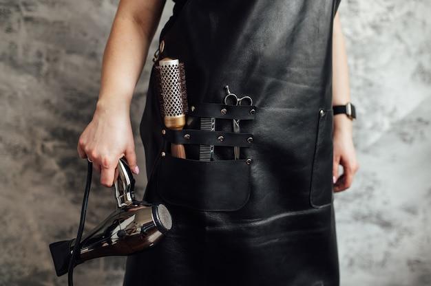 Человек в черном фартуке с профессиональным парикмахером на темном фоне крупным планом