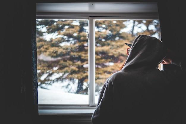 Человек в черной толстовке с капюшоном стоит у окна