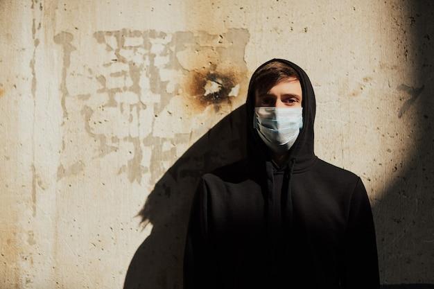 Человек в черной толстовке с капюшоном с медицинской маской в заброшенном здании у старой стены