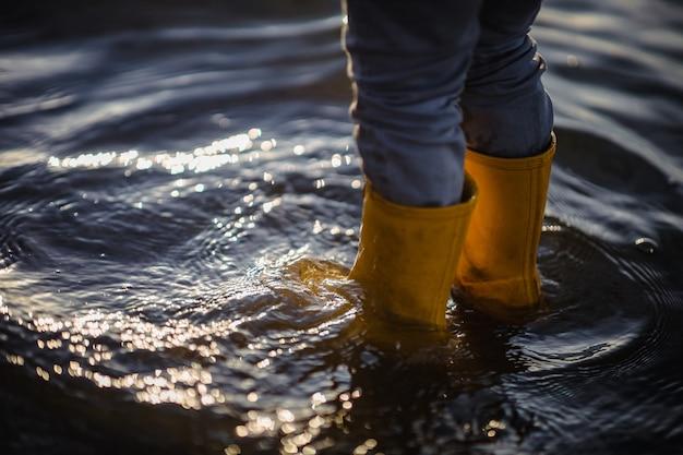 昼間に水の上に立っている青いデニムのジーンズと茶色のブーツの人