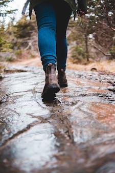 青いデニムジーンズと茶色の乾燥した葉の上に立っている茶色のハイキングブーツの人
