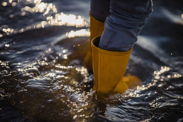 水の上に立っている青いデニムのジーンズと黄色のブーツの人
