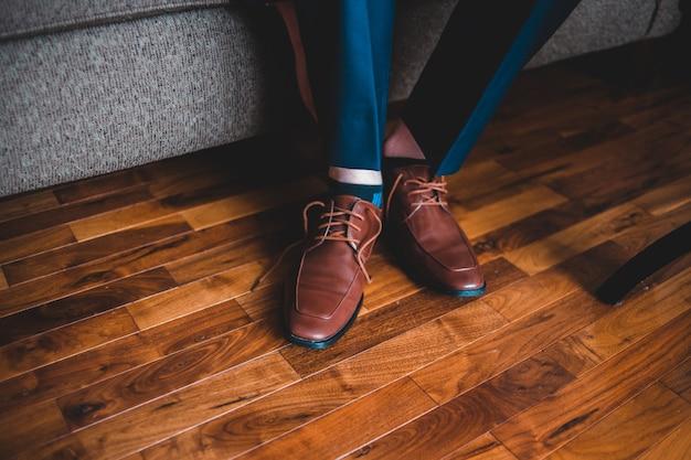 Человек в синих брюках и коричневых кожаных туфлях