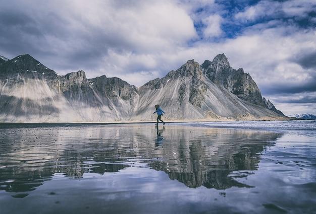 山の下の近くの湖の青いカヤックに立っている青いシャツと黒いズボンの人
