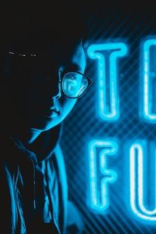 Человек в очках рядом с синими неоновыми вывесками