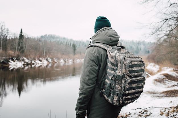 冬の間、木々に囲まれた湖の前の人