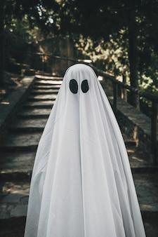 Человек в костюме призрак, стоящий в лесу