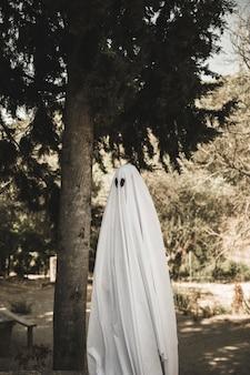 Человек в костюме призрак, стоящий возле дерева