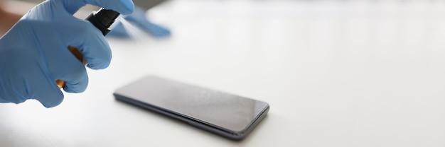 장갑을 낀 사람은 소독제 클로즈업으로 스마트폰을 취급합니다.