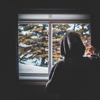 Человек в сером балахоне смотрит в окно