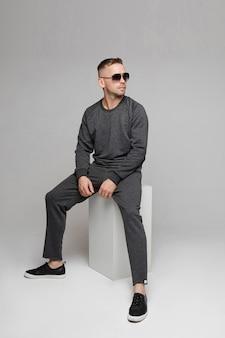 Человек в серой повседневной одежде и черных очках сидит на белом кубе и смотрит вдаль. концепция моды