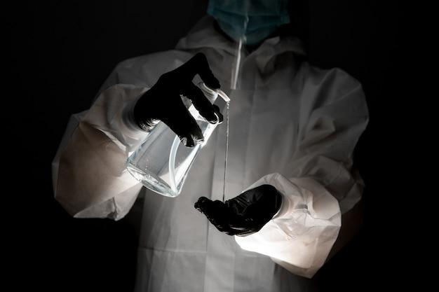 防護服を着た人が消毒剤のボトルを保持し、暗い部屋で手にそれを注ぐ