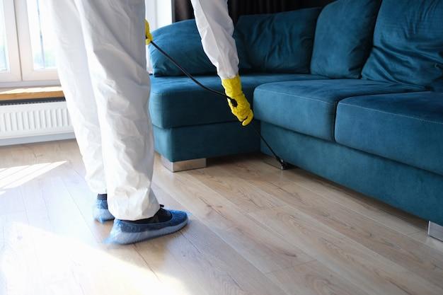 防護服と手袋をはめた人が、建物の痛みを伴う細菌消毒から部屋を治療しています...