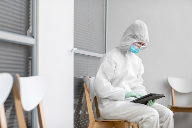 Человек в защитном костюме смотрит на планшет