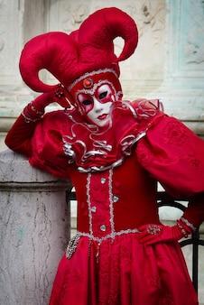 ハーレクインイタリアのコメディデルアルテ劇場の赤いカーニバル衣装の人
