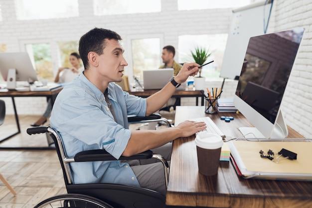 車椅子の人はコンピューターを注意深く見ます。