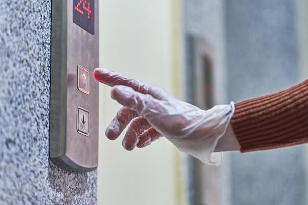 투명한 보호 장갑을 착용 한 사람이 엘리베이터 버튼을 누릅니다.