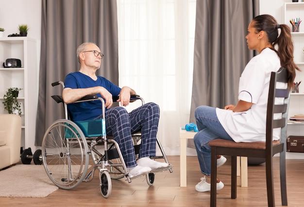 診察室で看護師と話しているwhellchairの人。ナーシングホーム支援、ヘルスケア、医療サービスの医療従事者と障害者