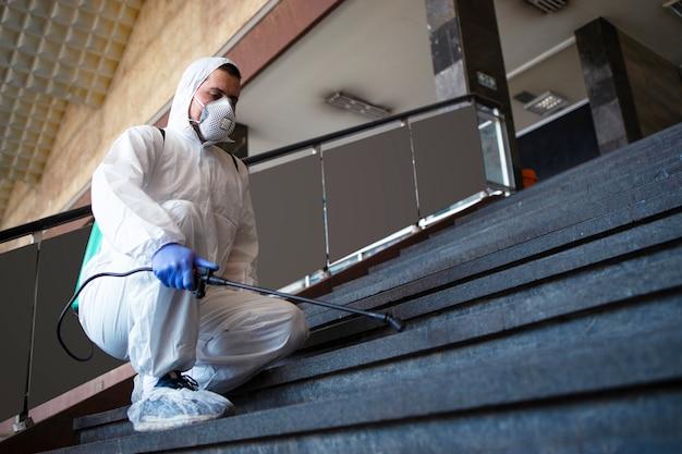 白い化学防護服を着た人が公共の廊下を消毒し、伝染性の高いコロナウイルスの拡散を阻止する手順
