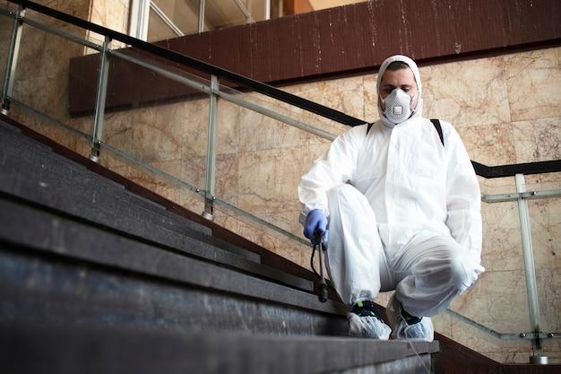 흰색 화학 보호 복을 입은 사람이 공공 복도를 소독하고 전염성이 높은 코로나 바이러스 확산을 막기위한 조치
