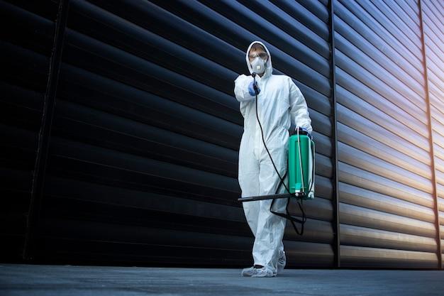 흰색 화학 보호 복을 입은 사람이 소독 및 해충 방제를 수행하고 독을 뿌려 곤충과 설치류를 죽입니다.