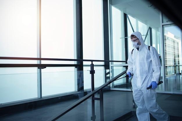 伝染性の高いコロナウイルスの拡散を防ぐために、公共エリアの消毒を行う白い化学防護服を着た人。