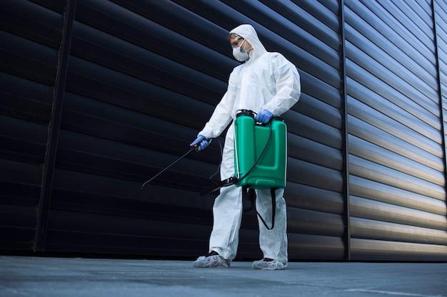 흰색 화학 보호 복을 입은 사람이 전염성이 높은 코로나 바이러스의 확산을 막기 위해 공공 장소를 소독하고 있습니다.