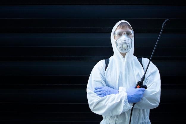 Человек в белом костюме химической защиты держит распылитель с дезинфицирующими химикатами, чтобы остановить распространение очень заразного вируса