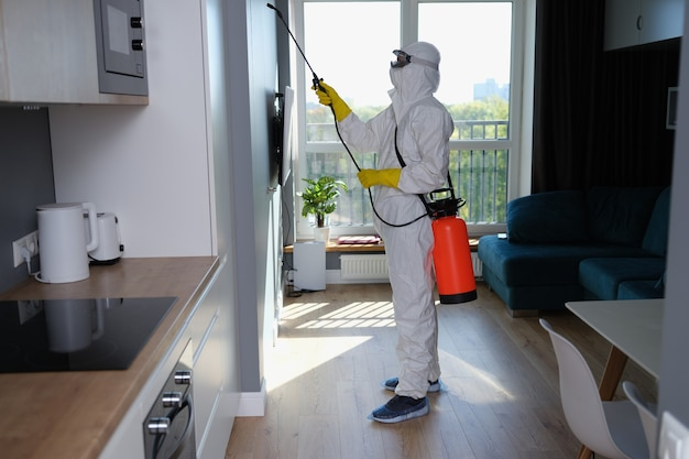 Человек в белой маске защитного костюма и перчатках с дезинфекцией на воздушном шаре на кухне
