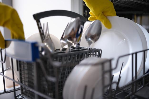 黄色い手袋をはめた人が食器洗い機からきれいな皿を取り出します