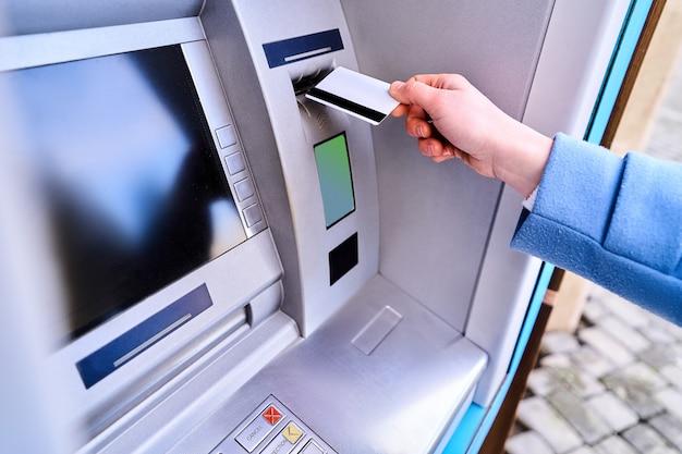 お金を引き出すために通りのatm銀行にプラスチックのクレジットカードを挿入する人
