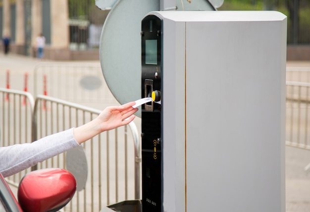 Person inserting into or removing ticket from parking machine.