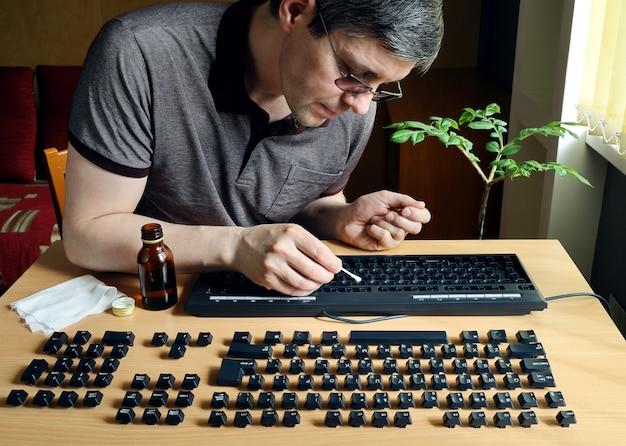 人はコンピュータのキーボードの内部を掃除するのに忙しい