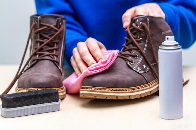 A person is cleaning men's suede casual boots with brush, rag and spray. shoe shine. footwear moisture and dirt protection