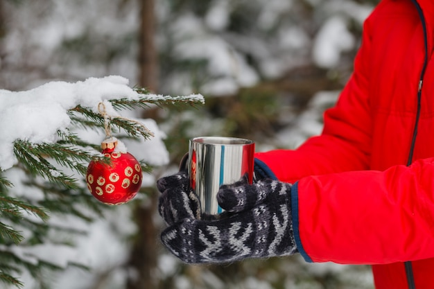 人は屋外の温かい飲み物のカップを保持しています。天気はとても寒く、マグカップは喫煙しています