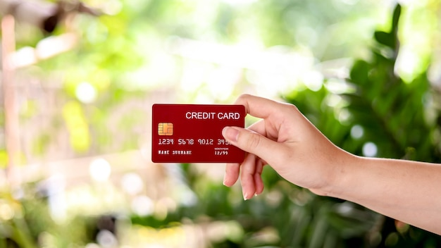 The person is holding a credit card, a credit card can be used to pay for goods and services at retail stores, restaurants, or online shopping. concept of using a credit card.