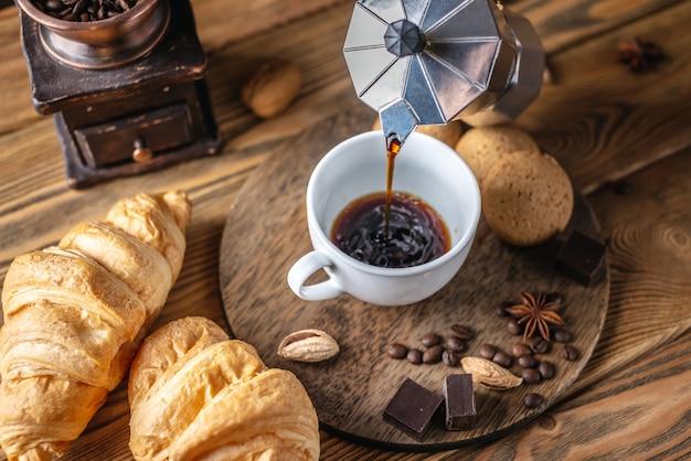 사람이 간헐천 커피 메이커에서 신선한 뜨거운 블랙 커피를 따르고 있습니다.