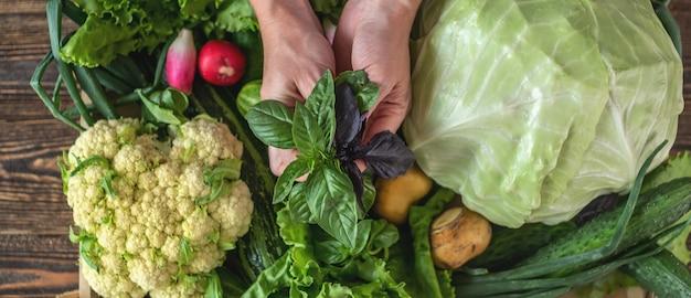 Человек берет из коробки базилик и свежие овощи