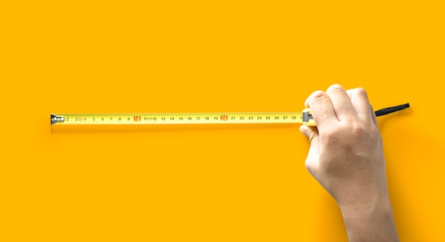 The person is using the length meter, tool for measuring length, isolated on yellow background and clipping path.
