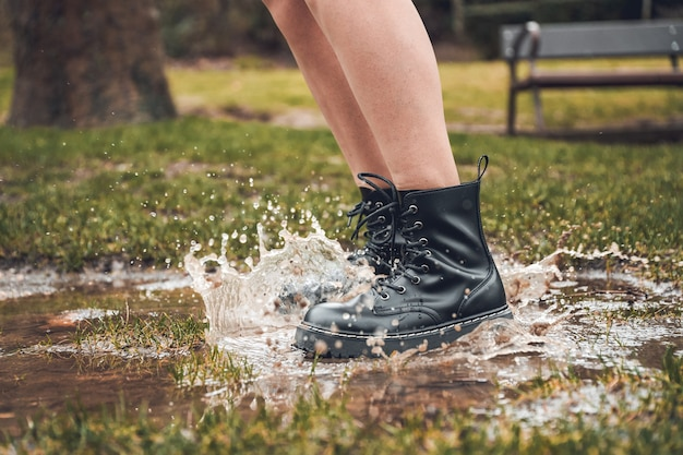 公園の水たまりを飛び越える人