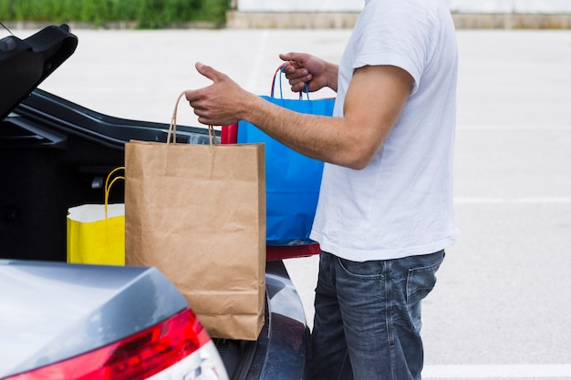 Person keeping shopping bags inside the car