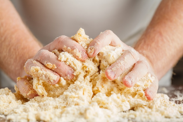 Person kneading dough on wooden table