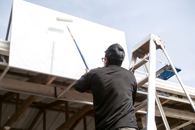 A person on a ladder painting a white sign or banner. copy space and mock up.