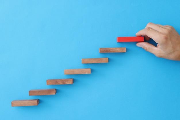 Человек кладет лестницу на синем фоне концепции управления бизнесом и организации