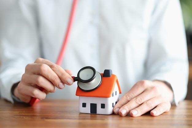 Человек слушает через стетоскоп стены и крышу дома