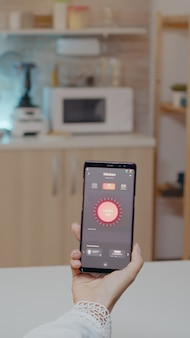 Person looking at mobile phone with lighting controlling app sitting in kitchen of house with automation light system, turning on bulb using voice command