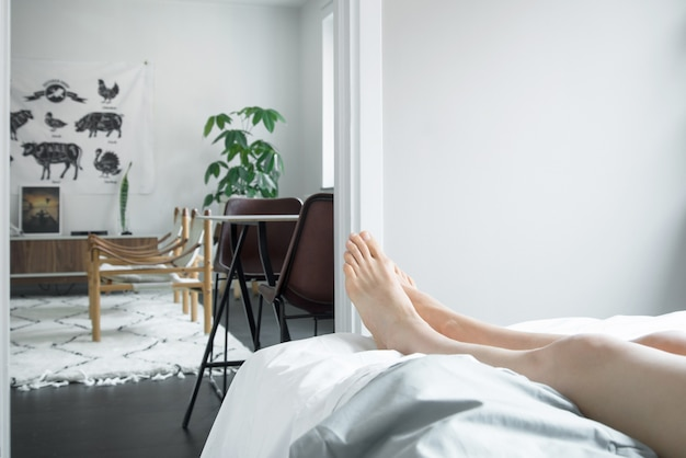 Person lying in the bed and relaxing during daytime