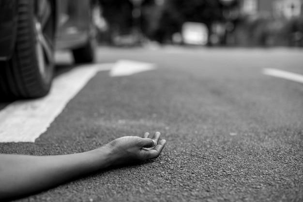 Человек, лежащий на земле после автомобильной аварии